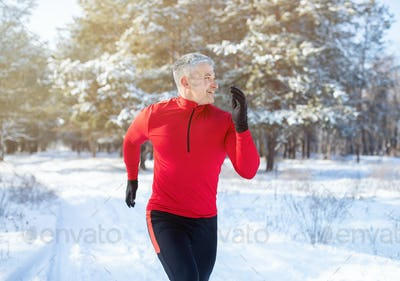 Mature trail runner training for marathon in beautiful snowy forest. Outdoor seasonal sports concept