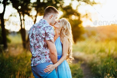 blonde girl with loose hair in a light blue dress and a guy in the light of sunset