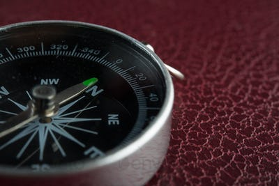 Compass over on red leather background. Travel concept.