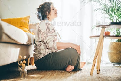 Plus size woman doing yoga and meditation at home.