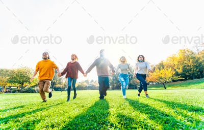 Multicultural people with open face mask running in the park after lockdown reopening