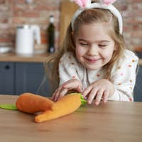 Playful girl steals a handmade carrot from the table