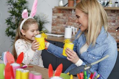 Happy mom and daughter playing with handmade Easter chickens