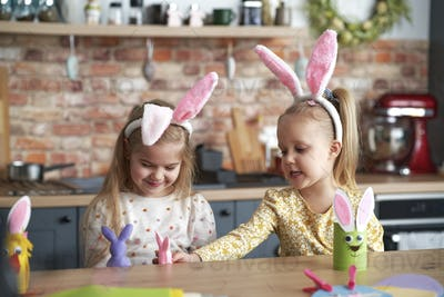 Happy two little girls have fun with Easter puppets
