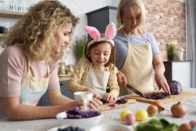 Three generations of women cooking together in the kitchen