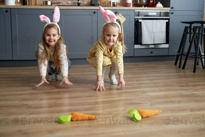 Two little girls playing handmade carrots on the floor