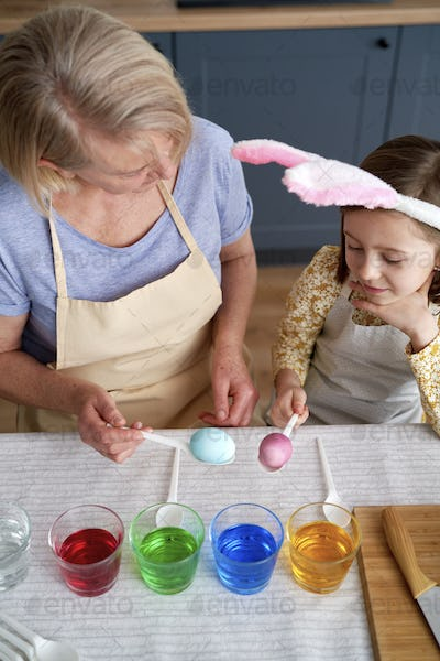 Top view of grandmother and granddaughter dyeing Easter eggs together