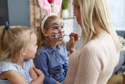 Mom painting Easter bunny on her daughter's face