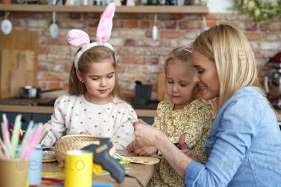 Mom with her daughters preparing Easter decorations at home
