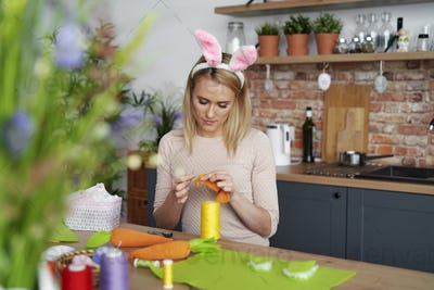 Beautiful woman in a rabbit's ears sews Easter decorations