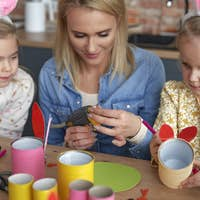 Close up of mom with two girls preparing Easter decorations
