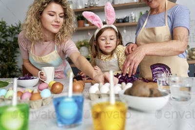 Three generation of women prepare natural dyes for coloring eggs