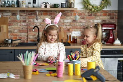Two little girls preparing decorations for Easter at home