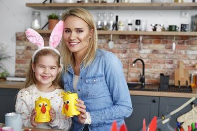 Portrait of smiling mother and daughter with handmade Easter chickens