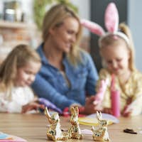 Close up golden easter bunnies and family in the background
