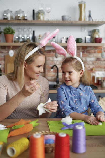 Mother and daughter in rabbit ears sewing Easter toys