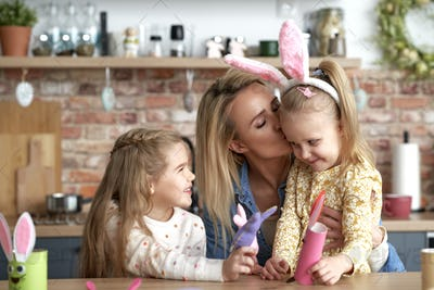 Cute kissing mom with her daughters during Easter fun