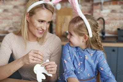 Mother and daughter in rabbit ears sewing Easter bunnies