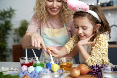 Mom and daughter dyeing Easter eggs in the kitchen
