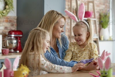 Mom and two small daughters with Easter accessories