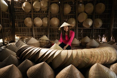 Asian traveler female craftsman making the traditional vietnam hat in the old traditional house