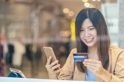 Asian woman using credit card with mobile phone for online shopping in department