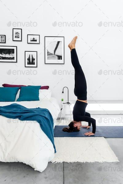 Fit woman practicing the tripod pose, (salamba sirsasana II) at her cozy home