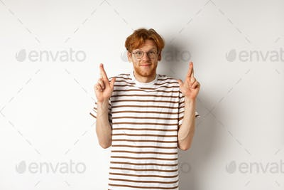 Hopeful young man with red hair and glasses cross fingers for good luck, making wish, standing over