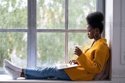 African woman student sitting on windowsill working on laptop, studying, holding mug coffee or tea.