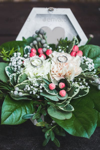 Two white gold wedding rings in casket close-up with fresh flowers for wedding ceremony