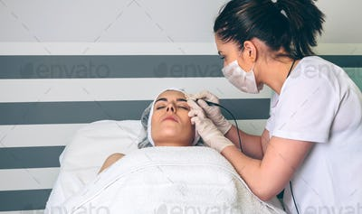 Female doctor doing getting rf lifting to woman in clinic