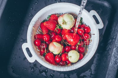 Ripe Fresh Berries and Fruits in black kitchen-sink under stream water. Summer Food Concept