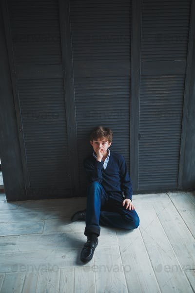 A teenager boy sitting on the floor.