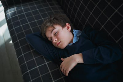 A boy teenager with closed eyes in a blue shirt lies on a blue couch in a white cage and sleeps.