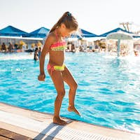 A little girl stands near the pool and tries the water with her foot