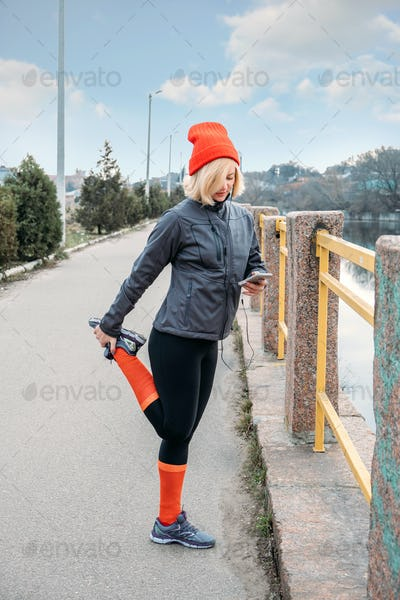 Outdoor Portrait of mature 40s fitness woman with smartphone and earphones standing in street after