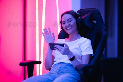 Young female teenage cyber sport gamer play mobile game by smartphone on eSport tournament