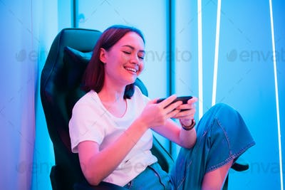Young female professional cybersport gamer play mobile game by smartphone on eSport tournament