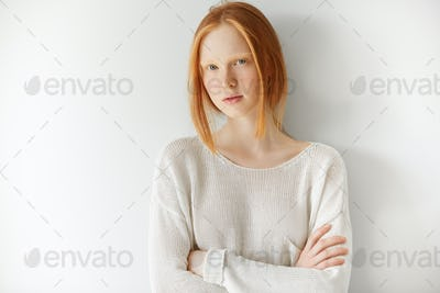 Redhead student girl with freckles looking at the camera with serious and thoughtful expression, pos