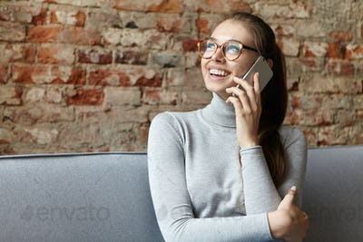 Pretty young fair-haired female with pony tail wearing big glasses and casual sweater sitting at coz