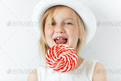 Nice little girl smiling at camera in white morning room, ready to lick red round lollipop. Joyful a