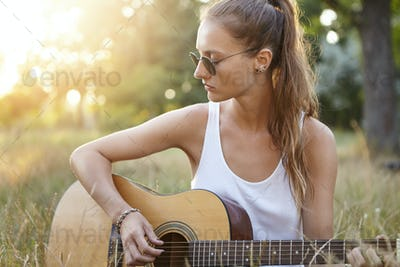 Talented girl dressed casually while sitting at greenland playing guitar looking aside with dreamy e