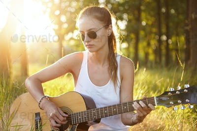 Outdoor portrait of beautiful teenage female with pony tail wearing glasses dressed casually playing