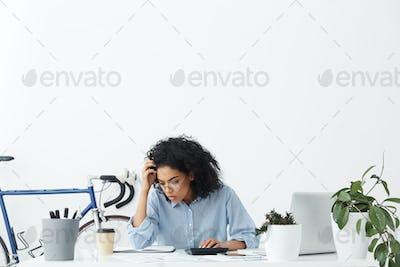 Serious dark-skinned woman accountant wearing formal shirt and eyeglasses calculating bills, sitting