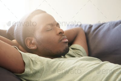 Sleeping handsome black man with full lips wearing black hat and green T-shirt having good dreames b