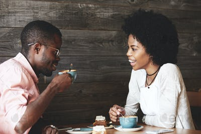 Young African American man in glasses drinking cappuccino with his beautiful girlfriend. Happy styli