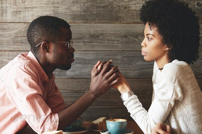African American young couple sitting at a cafe table: black man in glasses holding her beautiful wi