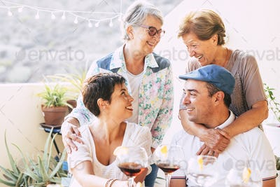 Group of caucasian friends with different ages and generations enjoy together the friendship