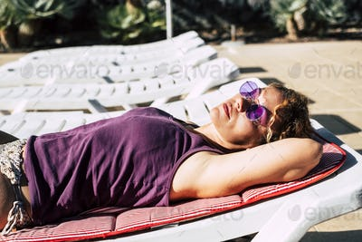Beautiful middle age caucasian woman lat down doing sunbath relax in summer on sunbeds