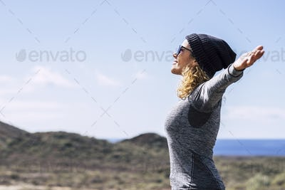 Happy full of joy beautiful caucasian woman with open arms enjoying the freedom